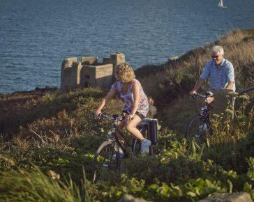couple cycling on cornish coastal path