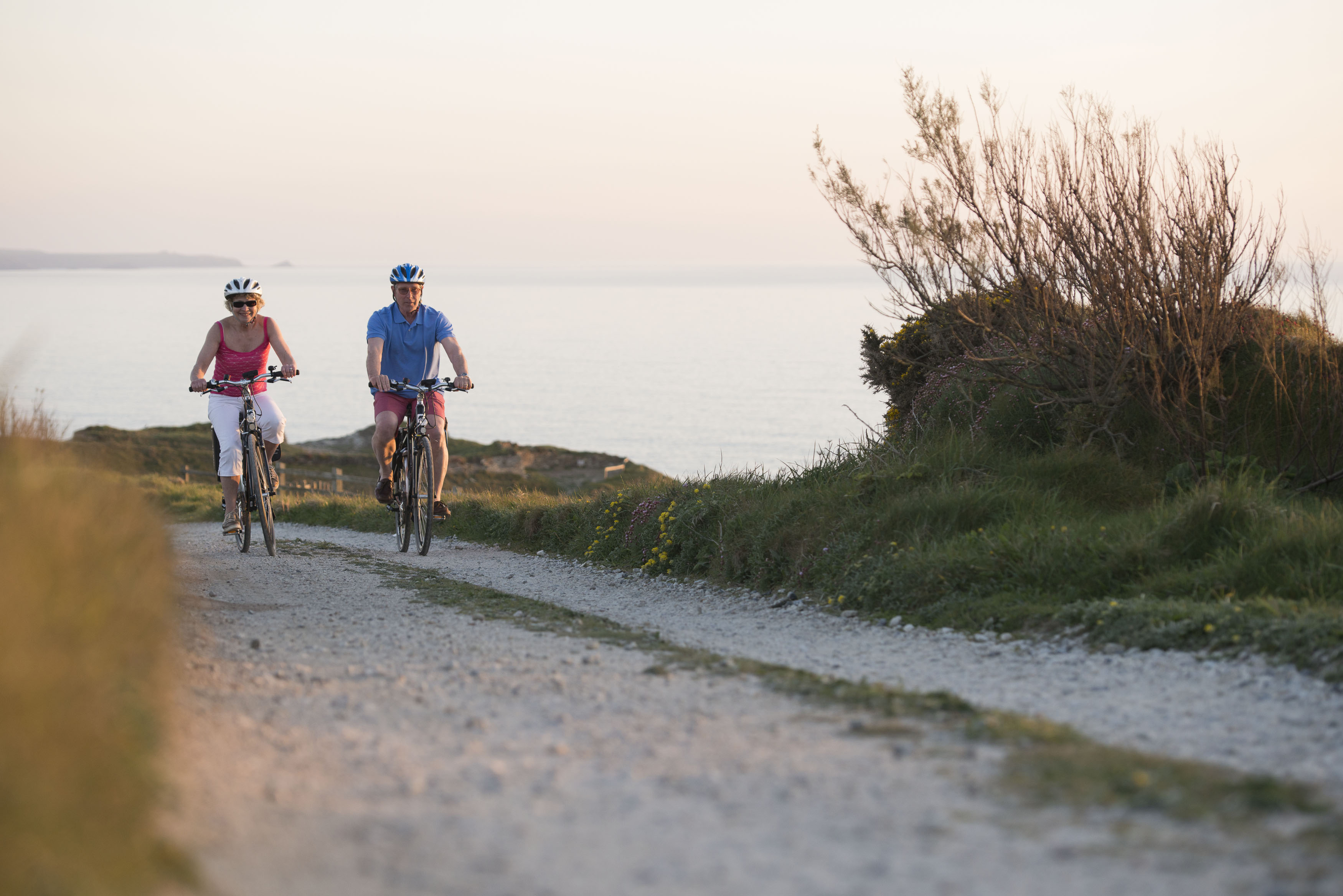 Couple cycling the Cornish coastline